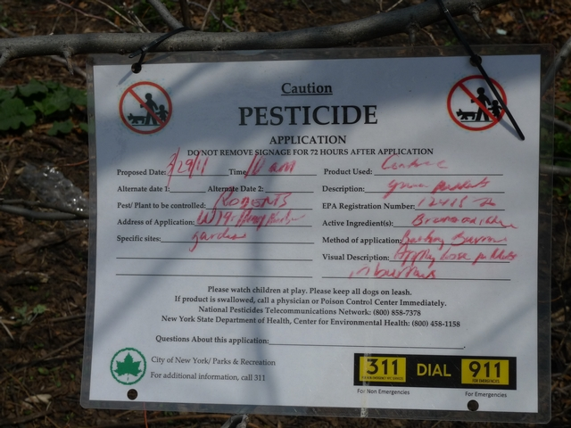 A sign near a dumpster in Riverside Park warns that rat poison was recently applied in the area.