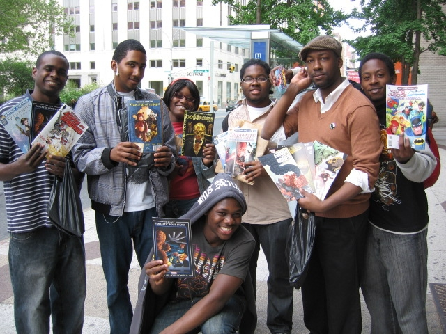A group of comic fans show off their haul from a day of comic book store-crawling on Free Comic Book Day.