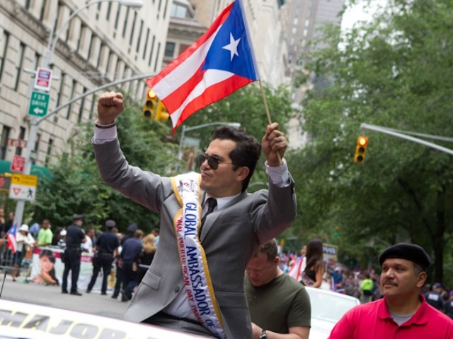 Funnyman John Leguizamo, the parade's global ambassador to the arts, gives a wave.