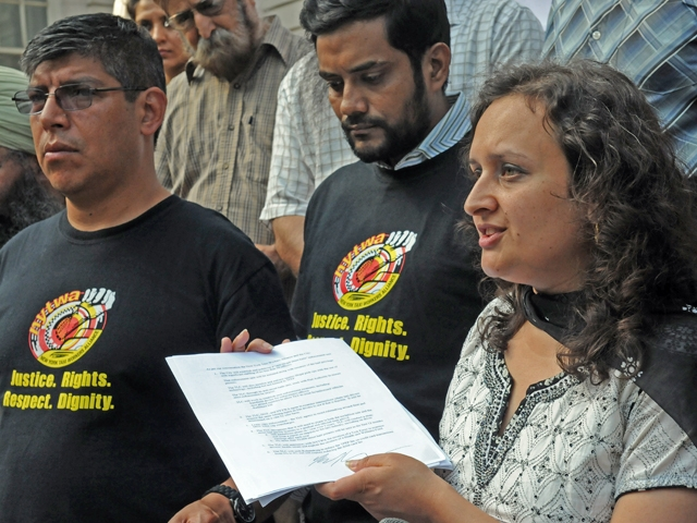 The New York Taxi Workers Alliance executive director, Bhairavi Desai, holds a copy of deal brokered with the city over the proposed livery car street hail plan at a city hall protest, June 20, 2011.