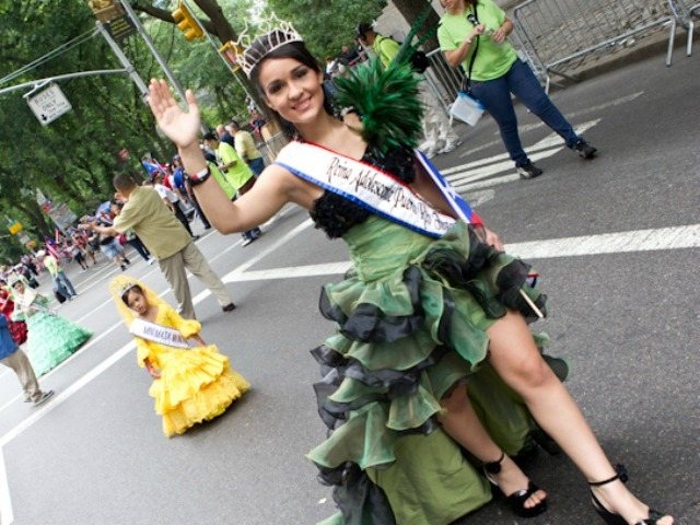 A beauty queen marches up the parade route.