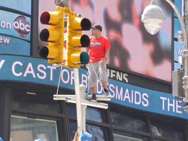 Unidentified man stands atop a traffic signal pole while rapping in Times Square Tuesday morning.