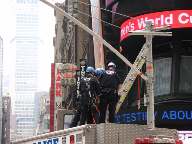 Police arrest man after he climbs down from atop a traffic signal post in Times Square on Tuesday.