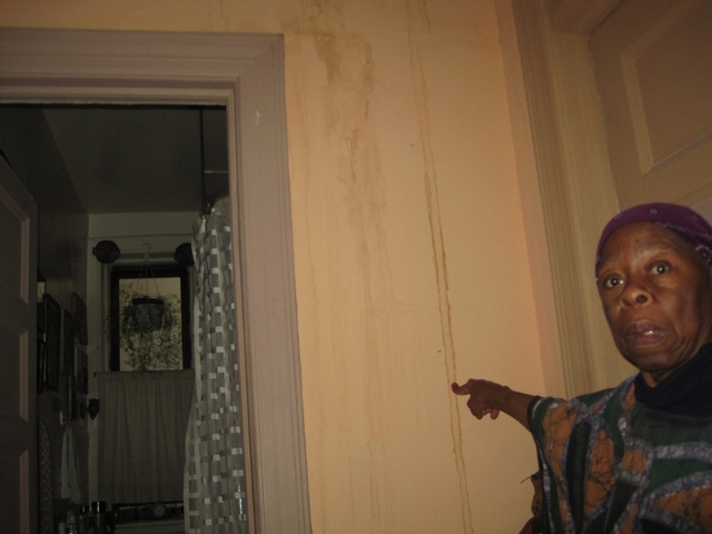 Rashidah Abu Bakr, a Tahl Propp tenant in Central Harlem, shows the water damage in her apartment from a flood she says was caused by improper construction in her building.