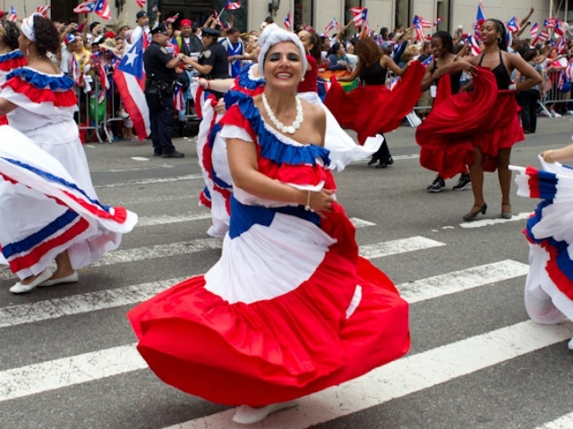 A woman in colorful dress dances along the parade route.