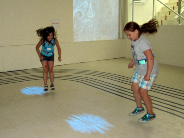 Kids follow moving lights on the floor, jumping to land in the center of them.