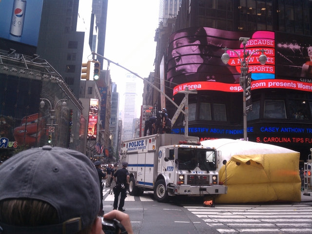 Police handcuffed a rapping man after he spent two hours on a light pole in Time Square forcing traffic closures.