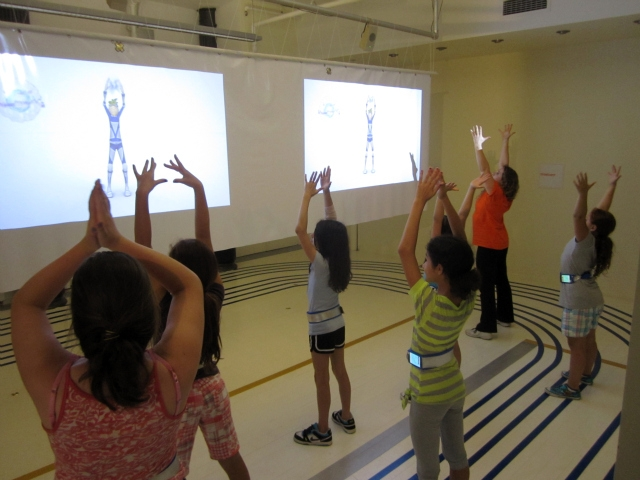 Kids follow on-screen avatars for warm-up instructions.