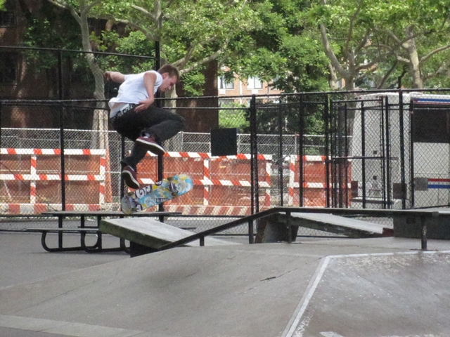 A skateboarder getting air at Coleman Skate Park under the Manhattan Bridge.