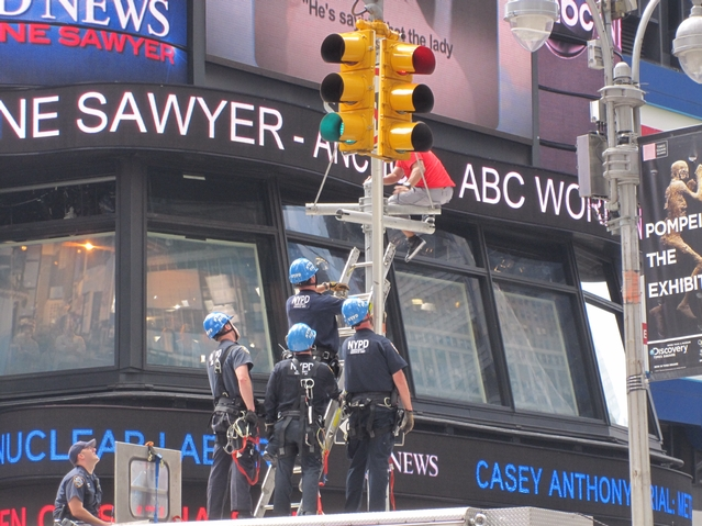 Police place a ladder to help coax an identified man into coming down from atop a light post in Times Square on Tuesday.