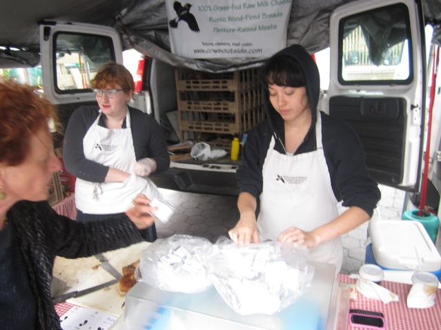 Cynthia Wennstrom (right), of Bobolink dairy, at the Union Square greenmarket, puts out a bag of pre-packaged cheddar.