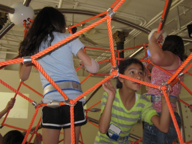 Kids pull themselves up the Climb-A-Thon structure, chasing blinking lights.