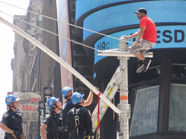 Police attempt to coax an unidentified man down from atop a traffic light pole in Times Square on Tuesdsay, June 28.