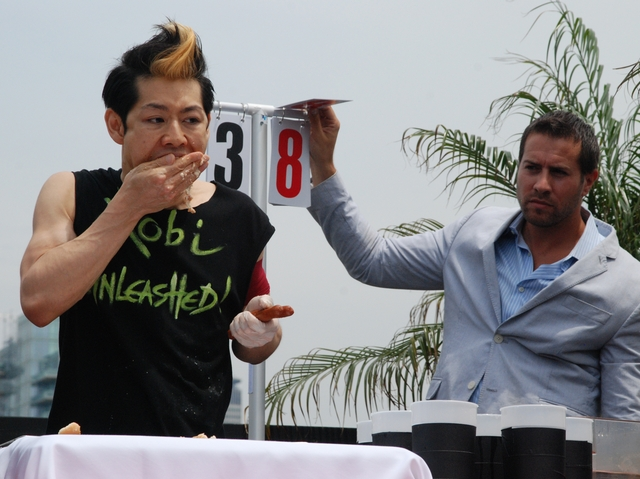 Kobayashi worked through one of the 69 hot dogs he ate Monday.