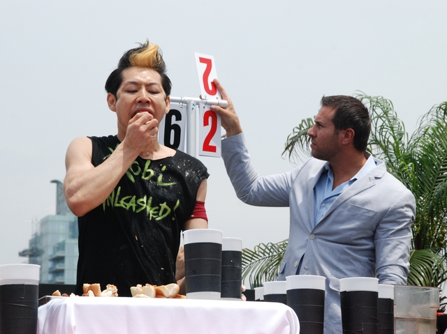 Takeru Kobayashi is at 65 dogs and counting during a dueling hot dog eating contest in the Flatiron District, July 4, 2011.