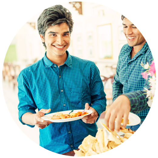 Student smiling, holding a plate of food