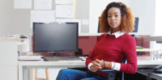 Confident career-driven woman sitting at a computer desk