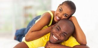 Woman laying on man, both smiling