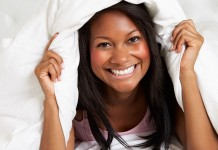 Girl smiling under blanket