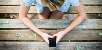 Girl on phone at picnic table