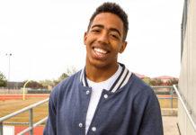 Happy boy standing on high school field