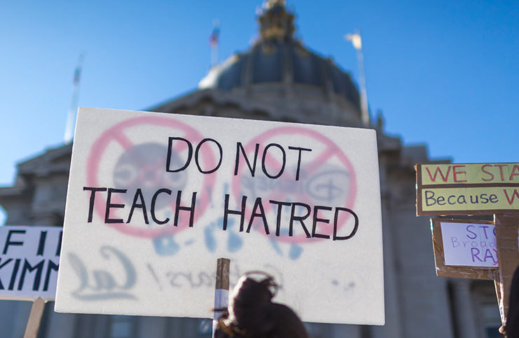 """Protestors in the street with a sign that says """"Do not teach hatred"""""""