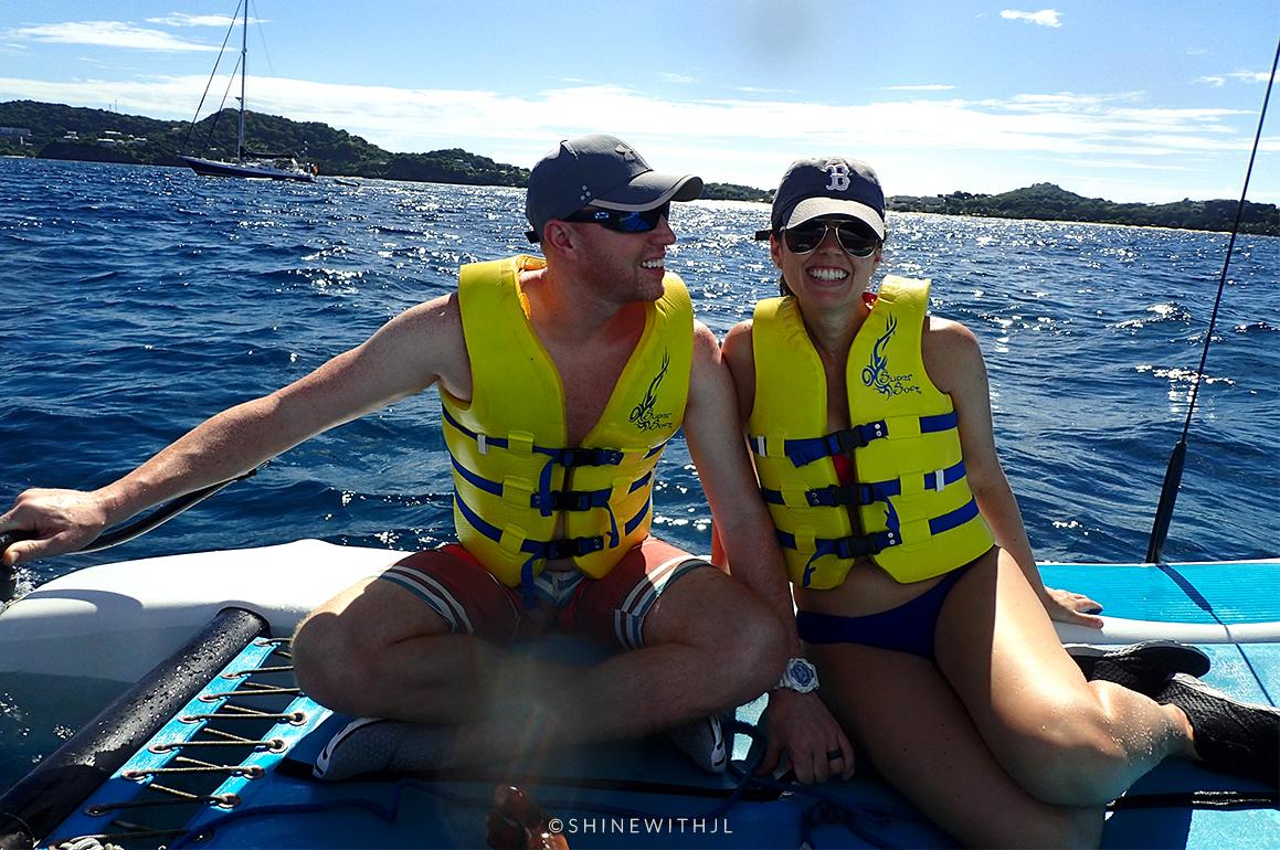 couple sailing on small catamaran sandals grenada review