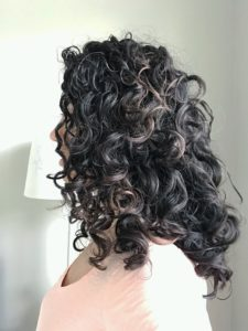 Dark curly brown hair with highlights