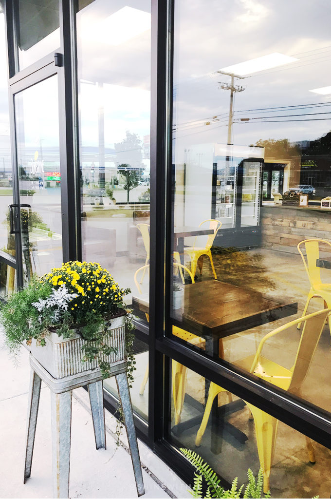 flower boxes outside yellow cafe chairs inside sunshine juice co