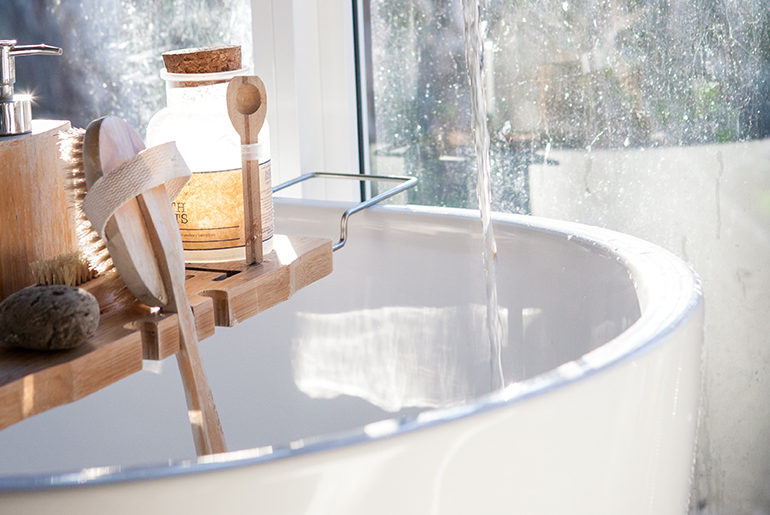white bathtub with wood accessories