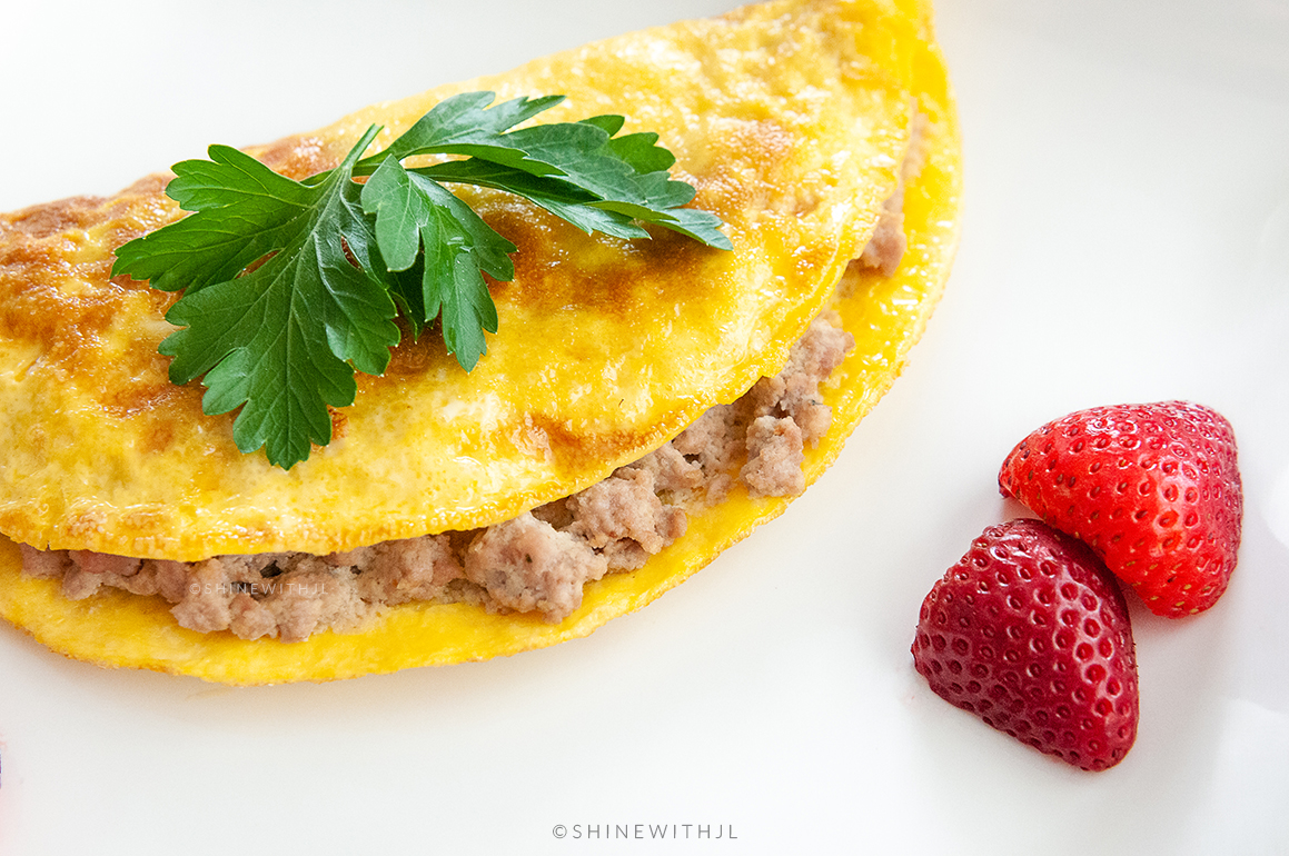 omelet with breakfast sausage and sliced strawberries
