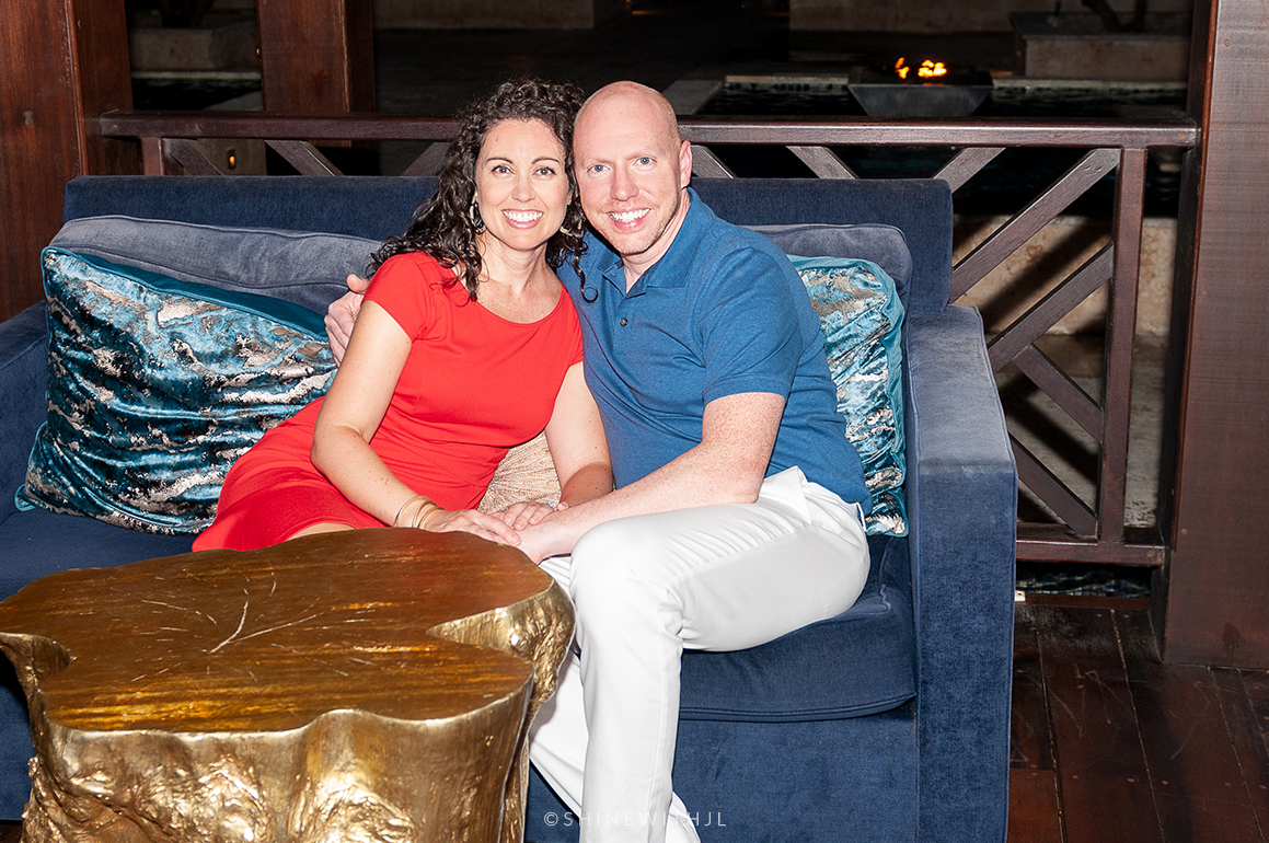 couple sitting on blue velvet couch at sandals grenada