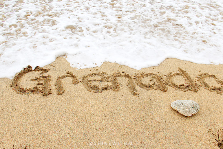 Grenada written in sand with ocean waves