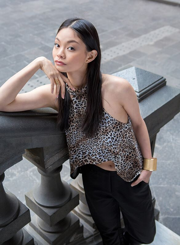 Walk on the wild side in a high-low leopard-print halter top and cropped satin trousers.