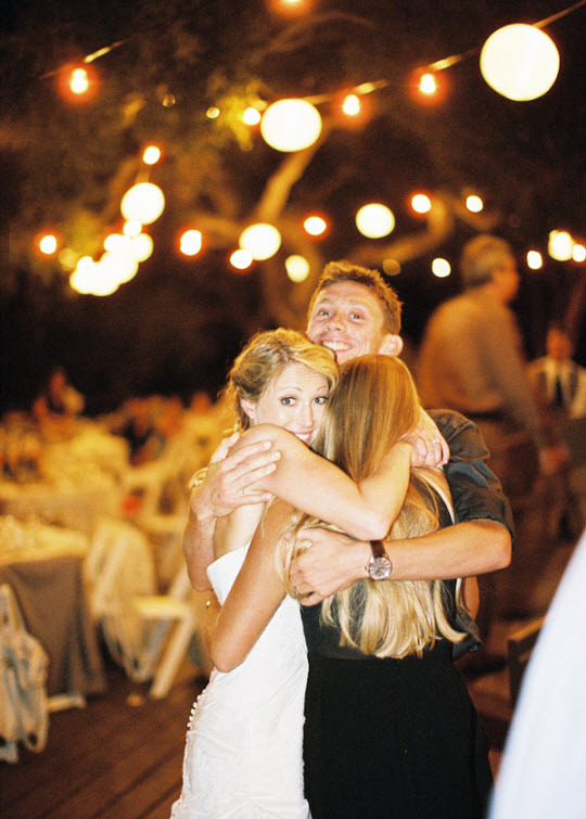 outdoor chic couple hugging string lighting