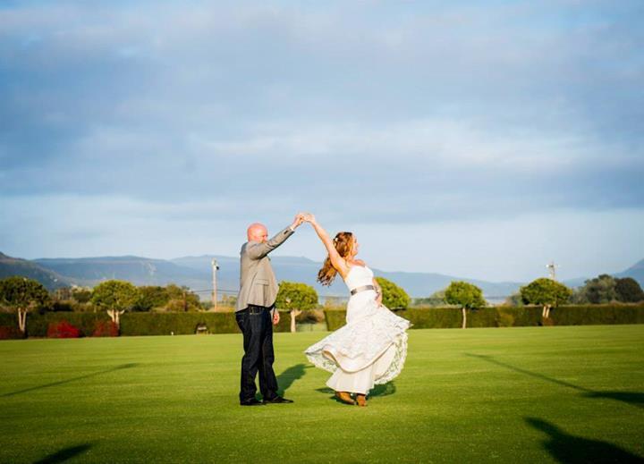 springtime rustic newlyweds dancing in field