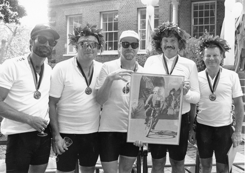 Leo Pickens, Jeff Morgan, Bob Gray, Christopher B. Nelson, and Jeffrey A. Bishop Wearing Bicycling Outfits, Medals and Wreathes, and Holding a Photograph of Albert Einstein on a Bicycle, Outside of McDowell Hall
