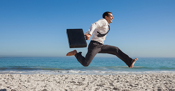Businessman running and jumping on the beach