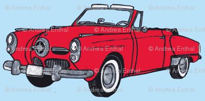 Giant red 1950 Studebaker convertible bullit nose on light blue background