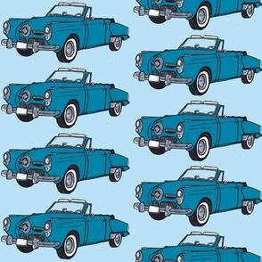 blue 1950 Studebaker convertible on light blue ground