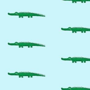 green crocodile with shadow, light aqua background