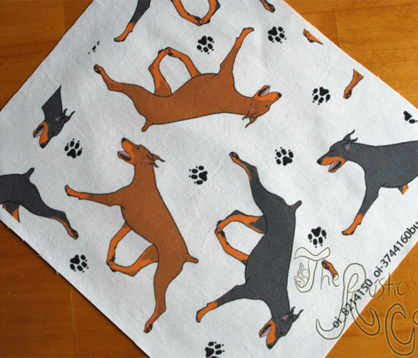 Trotting Doberman Pinschers and paw prints - white