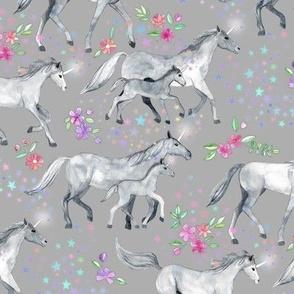 Mom and baby unicorns with stars on soft grey