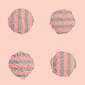 self-striping yarn balls in coral and grey on pink