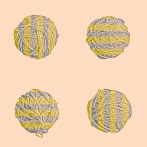 knitting a bumblebee:  stripey yarn balls in bronze and grey on peach