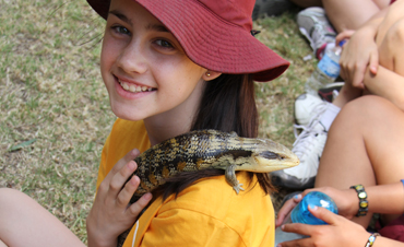 Schoolgirl smiling and holding a blue tongue lizard