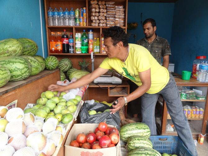 Raj Shrestha, the Director of Panchkhal Children's Home, buying fruit for the boys.