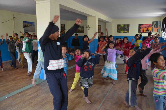 Hom Sir teaching the dance. The kids warm up with songs and exercises and then learn choreography to a Bollywood dance each class.