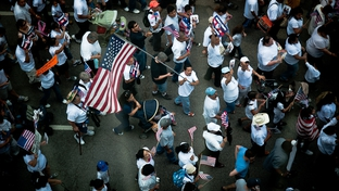 A demonstrator marches through the streets of downtown Dallas to protest the passage of Arizona's controversial new immigration law.