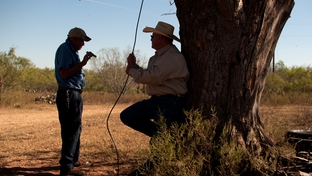 Victor Elizando and Noe Obregon rest in the shade during a visit to the farmland Obregon used to tend before the USDA's discriminatory loan practices put him out of business.